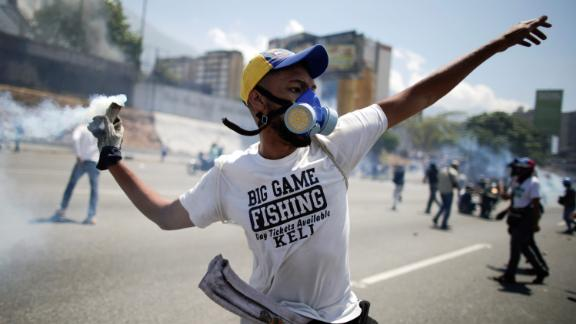 An opposition demonstrator throws back a tear-gas canister.