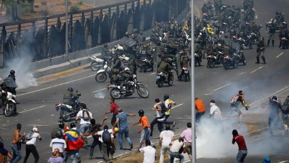 People who oppose Maduro confront troops who were firing tear gas at them outside the La Carlota airbase on April 30.