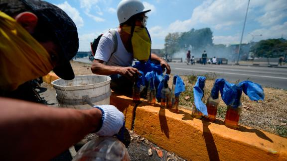 Opposition demonstrators prepare Molotov cocktails during clashes with soldiers loyal to Maduro.