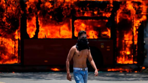 An anti-government protester walks near a bus that was set on fire by Maduro opponents on April 30.