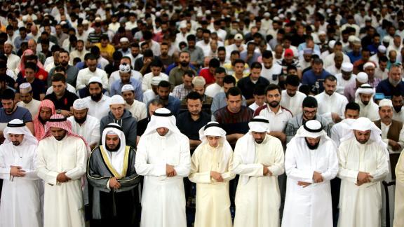 Muslim men pray in Kuwait City