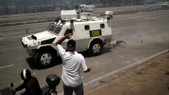 An opposition demonstrator is struck by a Venezuelan National Guard vehicle on a street near the La Carlota airbase on April 30.