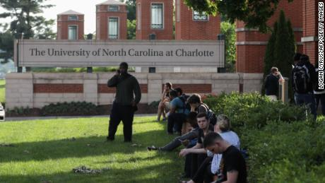 Students and faculty wait near the entrance of campus after a shooting on the campus of University of North Carolina Charlotte in University City, Charlotte, on April 30, 2019. - Six people were shot, two of them died on the University of North Carolina Charlotte campus. One person was taken into custody, according to police sources. (Photo by Logan Cyrus / AFP)        (Photo credit should read LOGAN CYRUS/AFP/Getty Images)
