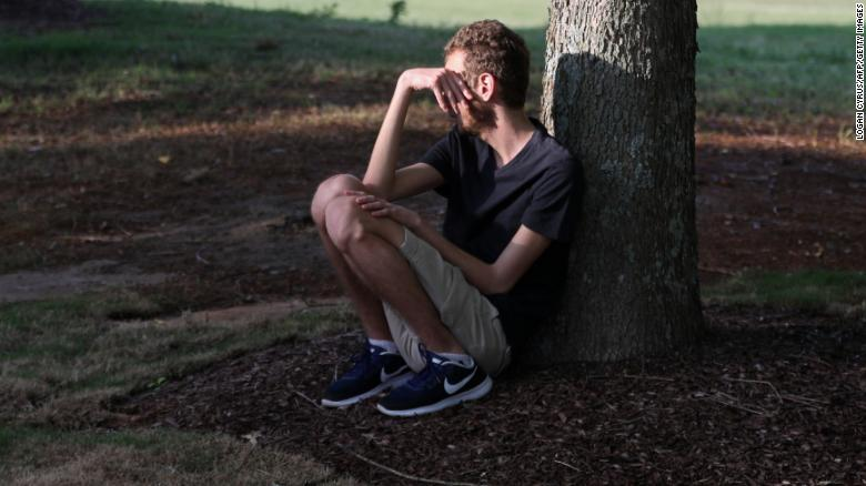 A student sits under a tree after a shooting on the campus of University of North Carolina at Charlotte.