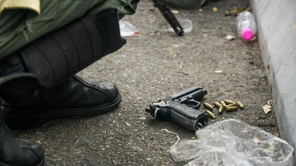 A handgun belonging to a soldier is seen on the ground, along with bullets.