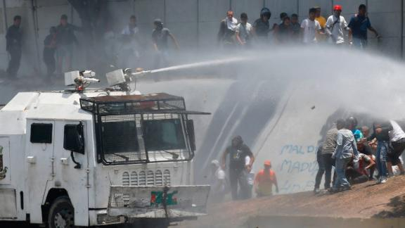 A Bolivarian National Guard water canon sprays opponents of Venezuela