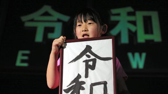 """A girl holds calligraphy reading """"Reiwa,"""" the name of the new imperial era."""