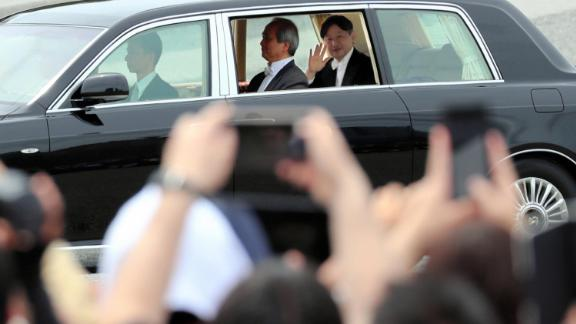 Naruhito waves to well-wishers.