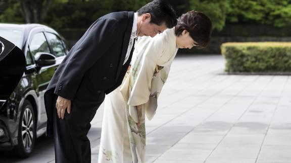 Japanese Prime Minister Shinzo Abe and his wife, Akie, bow as they arrive for Naruhito's ascension ceremony.