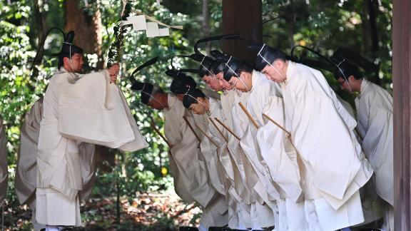 Shinto priests recite religious passages before entering the Meiji Shrine's main building for a ceremony on Wednesday. The ceremony reported the new emperor's enthronement to the royal family's ancestors.
