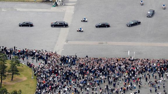 Naruhito's motorcade drives past crowds of well-wishers.