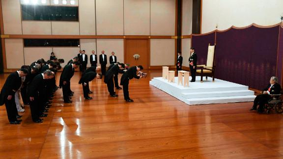 Naruhito, standing on a dais, inherits the imperial regalia.