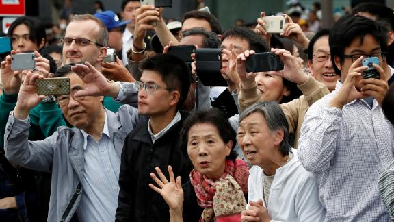 People take pictures as the royal family leaves the Imperial Palace.