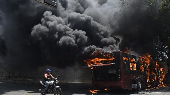 An opposition demonstrator passes by a government bus that was set on fire during clashes on April 30.