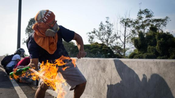A demonstrator throws a Molotov cocktail at National Guard security forces near the La Carlota airbase on April 30.
