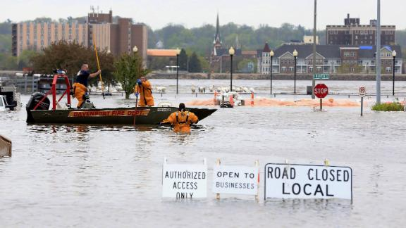 Davenport firefighters used a boat to ferry people from buildings surrounded by floodwater on Tuesday.