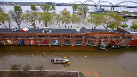 Firefighters walk a rescue boat down West River Drive along the freight house in Davenport on Tuesday, April 30.