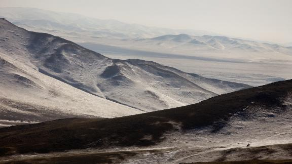 A Mongolian herder on horseback searches for his livestock along the frozen landscape in Bayantsogt, Tuv province in Mongolia.