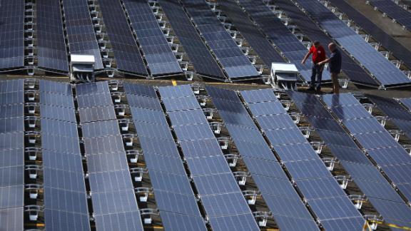 Men gesture next to solar panels set up by Tesla, at the  San Juan Children