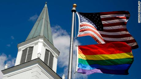 A gay pride rainbow flag flies along with the U.S. flag in front of the Asbury United Methodist Church in Prairie Village, Kan., on Friday, April 19, 2019. There's at least one area of agreement among conservative, centrist and liberal leaders in the United Methodist Church: America's largest mainline Protestant denomination is on a path toward likely breakup over differences on same-sex marriage and ordination of LGBT pastors. (AP Photo/Charlie Riedel)
