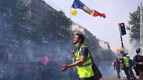 A 'yellow vest' protester holds a French flag during clashes with police on Wednesday.