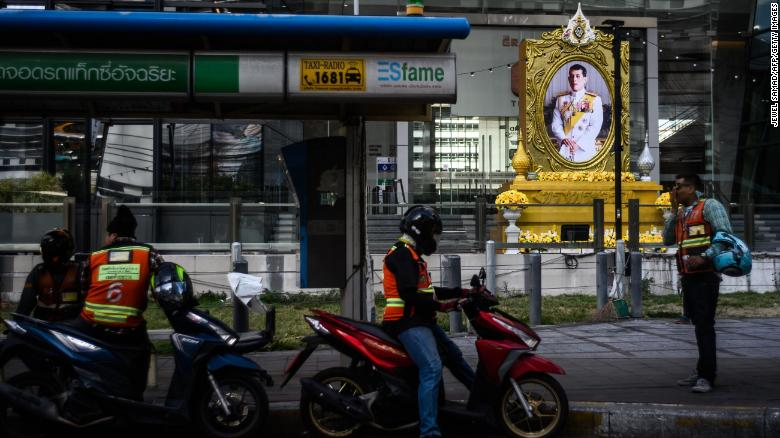 سائقي سيارات الأجرة بالدراجات النارية ينتظرون الركاب بالقرب من صورة لملك تايلاند مها فاجيرونجكورن في بانكوك يوم الأربعاء.