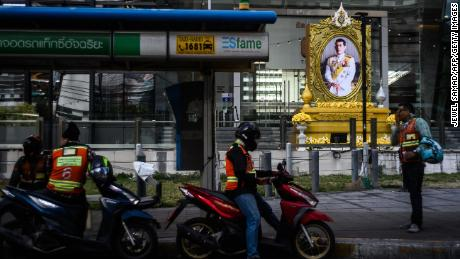 Motorbike taxi drivers wait for passengers near a portrait of Thailand & # 39; s King Maha Vajiralongkorn in Bangkok on Wednesday.