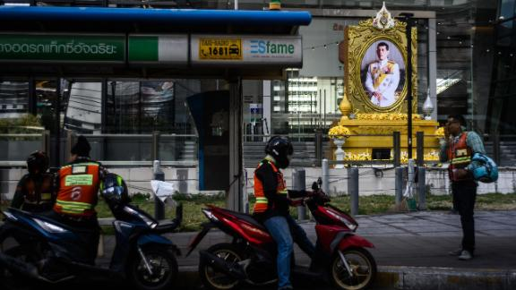 Motorbike taxi drivers wait for passengers near a portrait of Thailand's King Maha Vajiralongkorn in Bangkok on Wednesday.