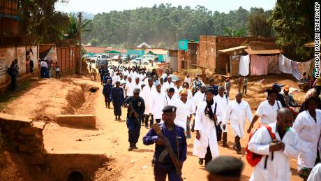 Doctors and health workers march in the Eastern Congo town of Butembo on Wednesday April 24, 2019, after attackers last week shot and killed an epidemiologist from Cameroon who was working for the World Health Organization. Doctors at the epicenter of Congo's Ebola's crisis are threatening to go on strike indefinitely if health workers are attacked again. (AP Photo/Al-hadji Kudra Maliro)