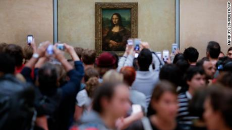 Visitors crowded in front of Leonardo da Vinci's painting 'Mona Lisa' at Musée du Louvre in Paris, Wednesday, June 1, 2016. (AP Photo/Markus Schreiber)