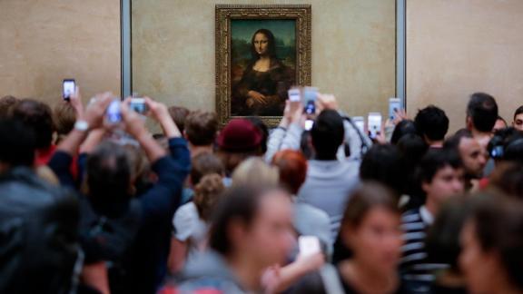 Visitors crowded in front of Leonardo da Vinci's painting 'Mona Lisa' at Musée du Louvre in Paris, Wednesday, June 1, 2016. (AP Photo/Markus Schreiber)