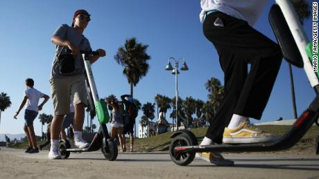 People ride Lime shared dockless electric scooters along Venice Beach on August 13, 2018 in Los Angeles, California.