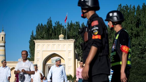 This picture taken on June 26, 2017 shows police patrolling as Muslims leave the Id Kah Mosque after the morning prayer on Eid al-Fitr in the old town of Kashgar in China's Xinjiang Uighur Autonomous Region.  The increasingly strict curbs imposed on the mostly Muslim Uighur population have stifled life in the tense Xinjiang region, where beards are partially banned and no one is allowed to pray in public. Beijing says the restrictions and heavy police presence seek to control the spread of Islamic extremism and separatist movements, but analysts warn that Xinjiang is becoming an open air prison. / AFP PHOTO / Johannes EISELE / TO GO WITH China-religion-politics, FOCUS by Ben Dooley        (Photo credit should read JOHANNES EISELE/AFP/Getty Images)