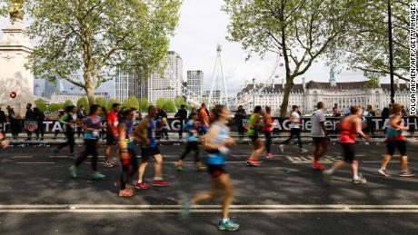 Competitors run along The Embankment with the London Eye seen in the background during the 2019 London Marathon on April 28.