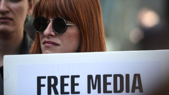 """A journalist holds a placard reading """"free media"""" during a demonstration for the World Press Freedom Day on the Istiklal avenue, in Istanbul, on May 3, 2017. According to the P24 press freedom website on April 4, 2017, there are 141 journalists behind bars in Turkey, most of whom were detained as part of the state of emergency imposed after the failed coup."""