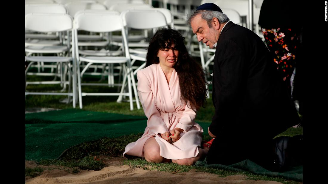 "Hannah Kaye, the daughter of <a href=""https://www.cnn.com/2019/04/28/us/california-synagogue-shooting-victims/index.html"" target=""_blank"">shooting victim Lori Kaye,</a> cries as she sits alongside her father, Howard, at her mother's grave in San Diego on Monday, April 29. Lori Kaye was killed two days earlier when a man opened fire inside a synagogue in Poway, California. She was 60 years old."