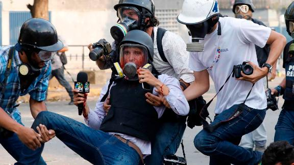 Journalists carry reporter Gregory Jaimes, who was injured Wednesday, May 1, while covering clashes between security forces and anti-government protesters in Caracas.