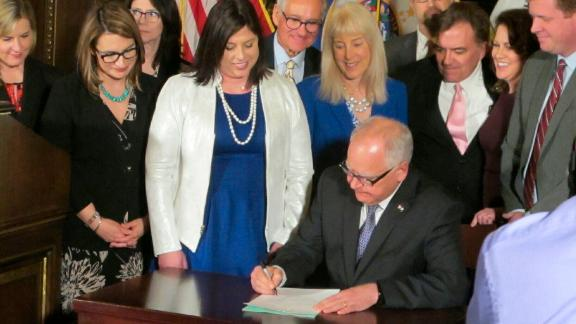 Jenny Teeson, center, in white, looks on as Minnesota Gov. Tim Walz signs a bill repealing a law that prevented prosecutors from filing sexual assault charges against people accused of raping their spouse.