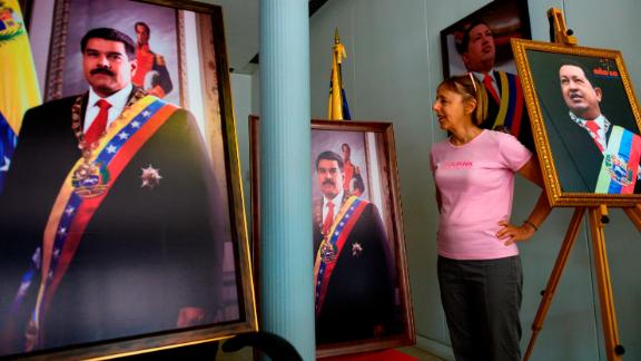 CODEPINK activist Medea Benjamin speaks to reporters, surrounded by pictures of former President of Venezuela Hugo Chavez and current president Nicolas Maduro, near the entrance of the Venezuelan embassy in Washington, DC on April 19, 2019. - Activists opposed to supporters of Venezuelan opposition leader Juan Guaido and their takeover of diplomatic buildings belonging to the Venezuelan government of Nicolas Maduro have been staging a 24/7 vigil to protect the Venezuelan Embassy in Washington DC. (Photo by Andrew CABALLERO-REYNOLDS / AFP)        (Photo credit should read ANDREW CABALLERO-REYNOLDS/AFP/Getty Images)