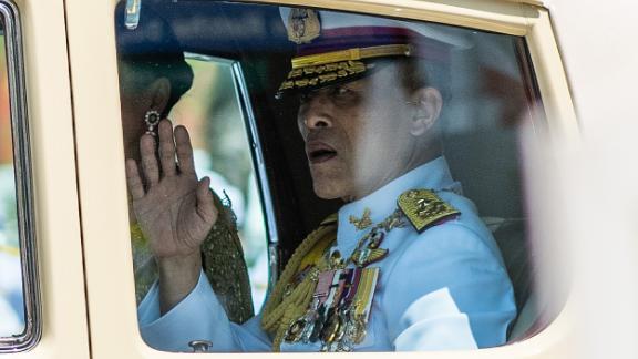 King Maha Vajiralongkorn waves to onlookers as he arrives at the Grand Palace for his coronation.