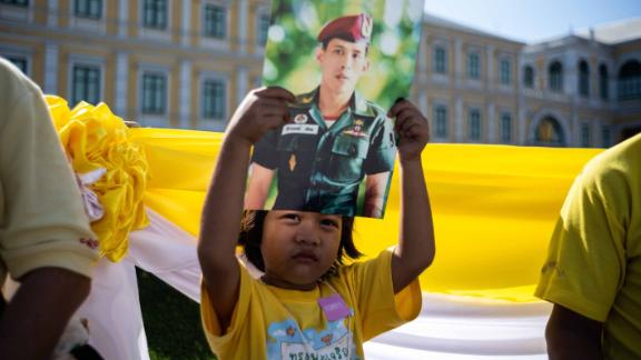 A child holds a portrait of King Vajiralongkorn as she waits with others near the Grand Palace during the coronation on May 4.