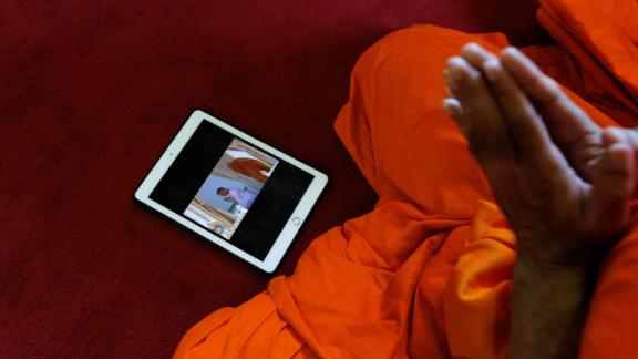 A tablet displaying King Maha Vajiralongkorn undergoing a royal purification ritual is seen as a Buddhist monk prays during the King's coronation on Saturday.