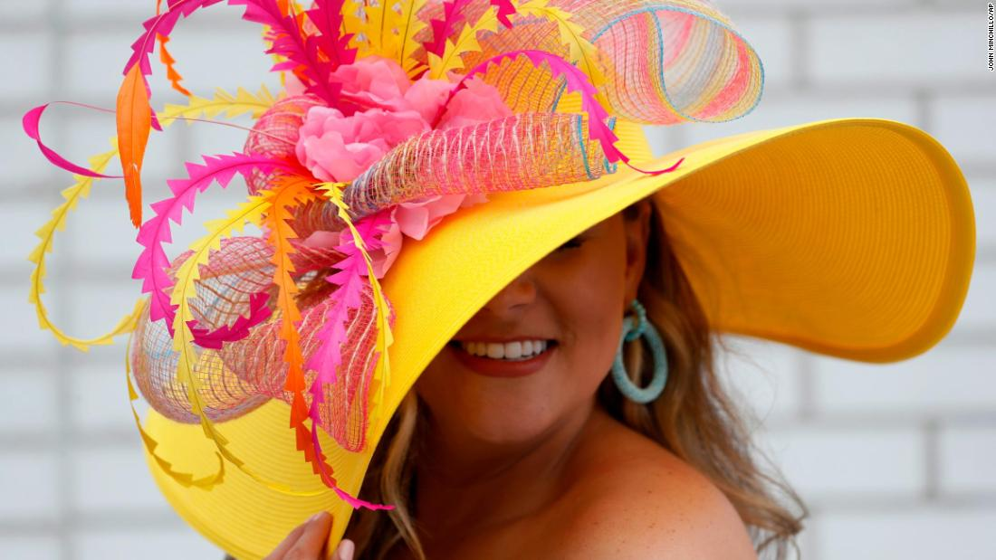 A woman shows off her pink and yellow hat.