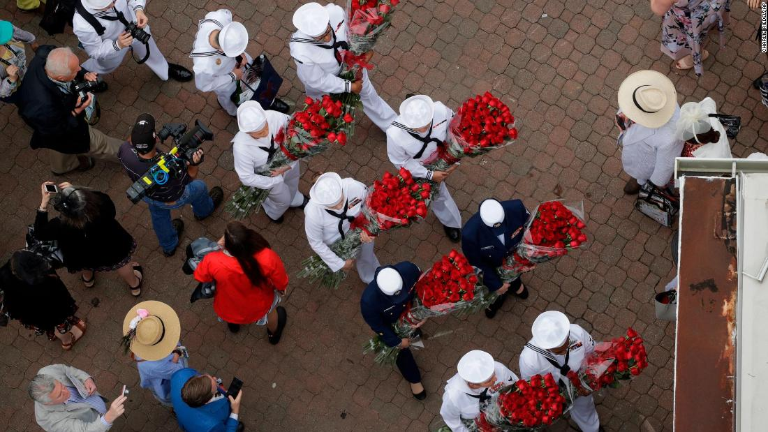 US Navy sailors arrive at Churchill Downs carrying roses before the Kentucky Derby.