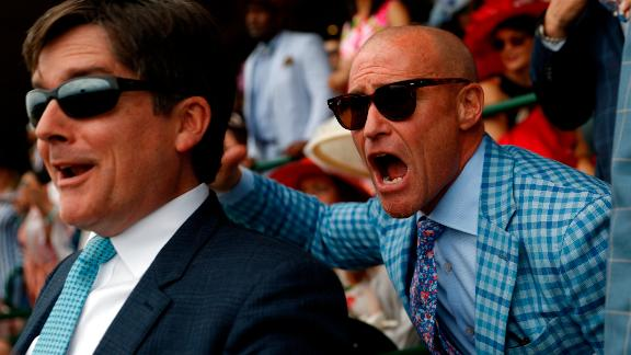 People cheer as they watch a race at Churchill Downs prior to the 145th running of the Kentucky Derby on Saturday, May 4.
