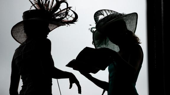 Women wearing extravagant hats read a pamphlet before the Kentucky Derby.