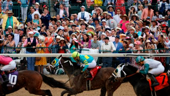 People cheer as they watch a race at Churchill Downs before the 145th running of the Kentucky Derby.