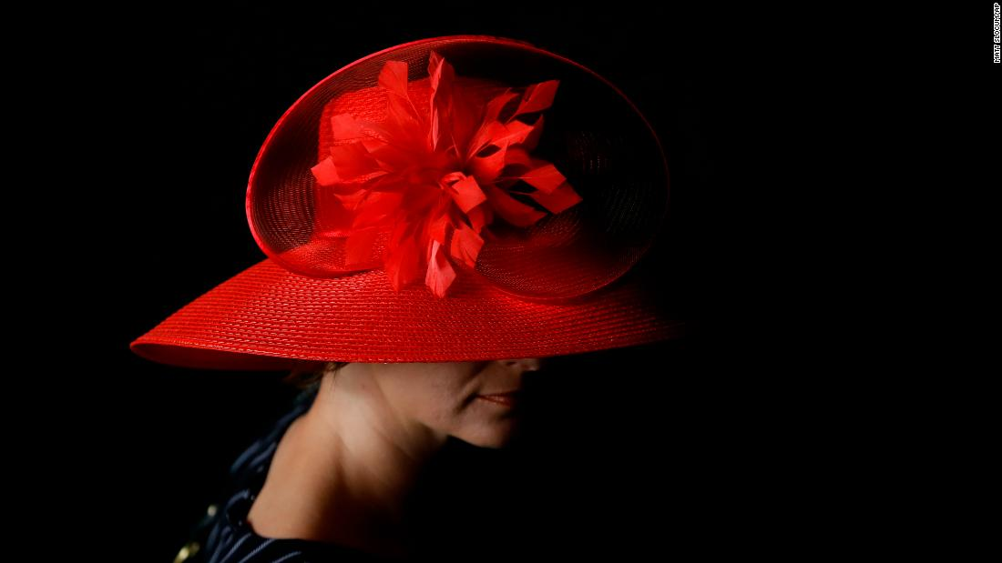 A woman wears a red hat before the Kentucky Derby.