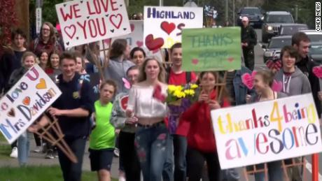 Students carrying signs and flowers walked together to Davidson's home, stood on their lawn, and kissed them collectively.