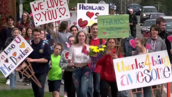 Students carrying signs and flowers walked together to Davidson's home, stood on her lawn and blew her a collective kiss.
